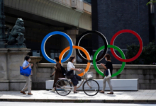 People walk by the Olympic rings installed by the Nippon Bashi bridge in Tokyo (AP)