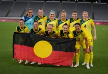 Australia players pose for a photo with an indigenous flag prior to the football match against New Zealand (AP)