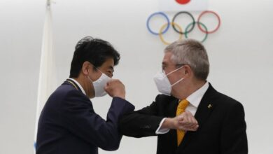 IOC president Thomas Bach and Japan's former prime minister Shinzo Abe bump fists after Abe was awarded the Olympic Order (AFP)